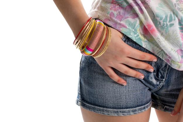 반바지 주머니에 여자의 손입니다. 블루 데님 반바지와 팔찌. 밝은 색상의 캐주얼 액세서리. 스트라이프 패턴의 팔찌.