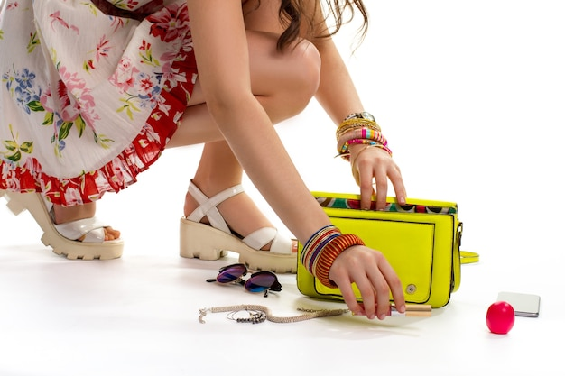 Lady's hand takes lipstick. necklace near lime handbag. cosmetic accessories and trendy clothes. what's inside woman's bag.