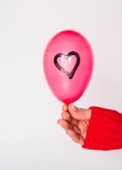 Леди рука с воздушным шаром с окрашенным сердцем