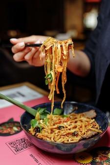 お箸で女性の手。女性の手は牛箸で麺を取る