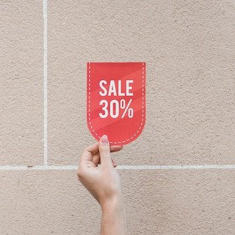 Lady's hand with red sale sign
