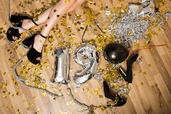 Lady's legs in evening shoes on floor between balloons numbers and tinsel