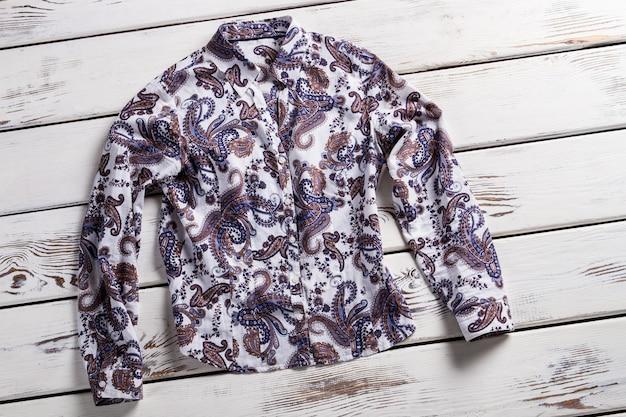 レディース長袖フローラルシャツ。白い木製の棚にシャツ。古いテーブルの上の新しい衣服。白い床に横たわるシャツ。
