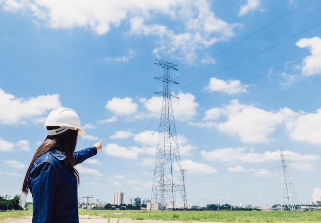 Lady in safety helmet pointing at high voltage line