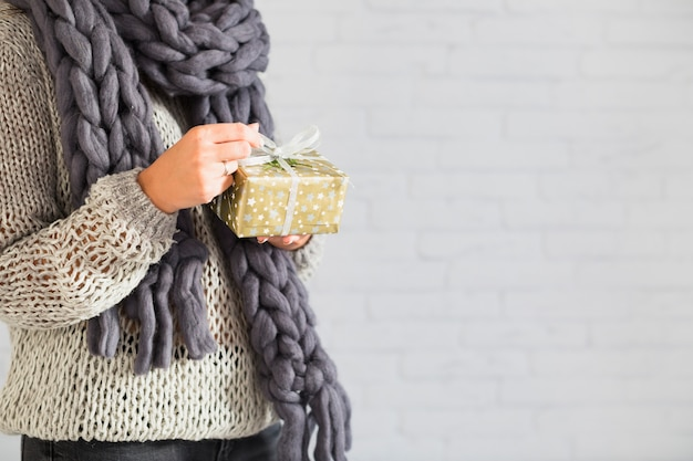Lady in scarf with gift box in hands