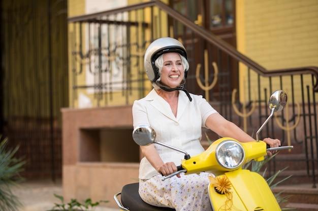 Lady on scooter wearing helmet.