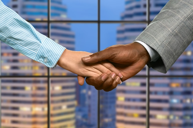 Lady shakes black businessman's hand. woman's handshake on skyscraper background. give him a second chance. appreciate what you have.