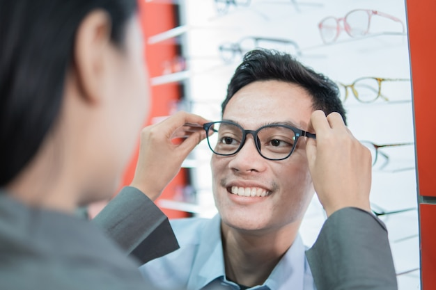 A lady shop assistant puts new glasses on to a male customer at an optician