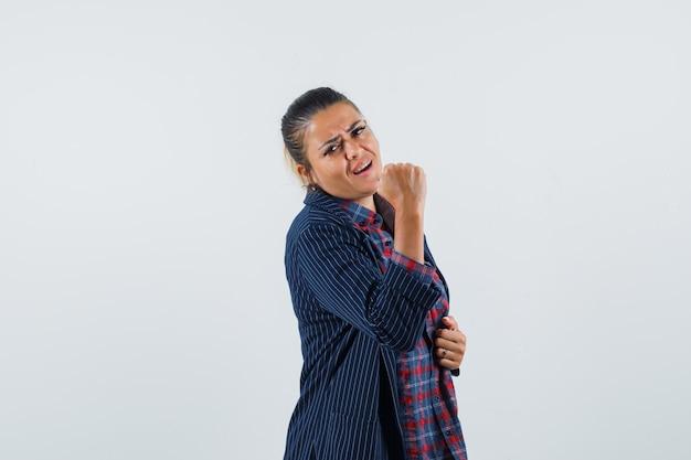 シャツ、ジャケットでくいしばられた握りこぶしを示し、自信を持って見える女性、正面図。