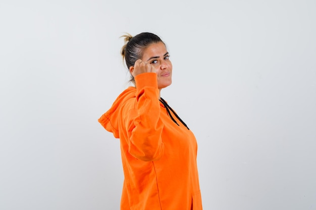 Lady showing clenched fist in orange hoodie and looking confident .