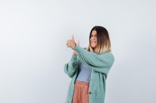 カジュアルな服装で二重の親指を見せて、満足そうに見える女性、正面図。