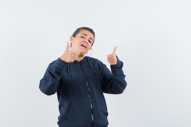 パーカーで二重の親指を示し、自信を持って見える女性。正面図。