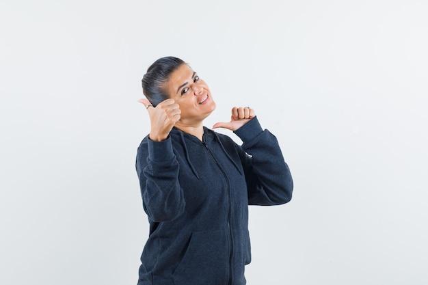 Леди показывает двойные пальцы вверх в толстовке с капюшоном и выглядит счастливой