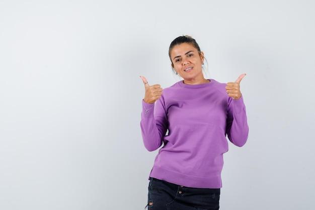Signora che mostra il doppio pollice in alto in camicetta di lana e sembra allegra