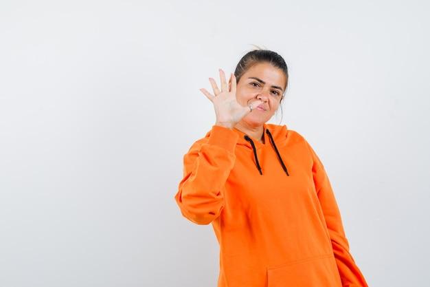 Дама показывает пять пальцев в оранжевой толстовке с капюшоном и выглядит уверенно