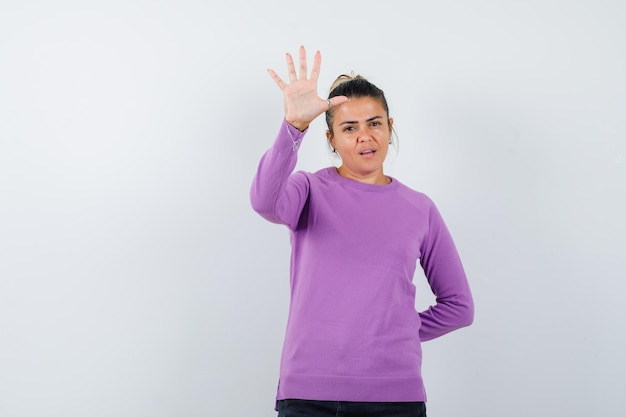 Lady showing five fingers in wool blouse and looking confident