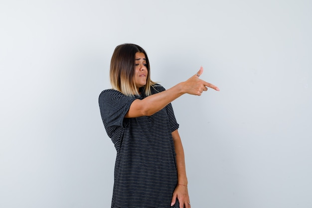 Lady showing gun gesture in black t-shirt and looking focused , front view.