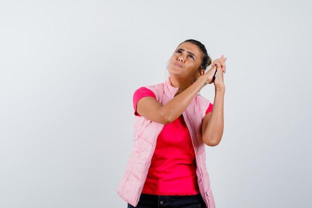 Леди показывает жест пистолета в футболке, жилете и выглядит задумчиво