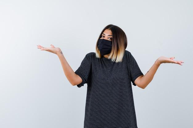 Signora che mostra gesto impotente in abito nero, mascherina medica e sembra esitante. vista frontale.