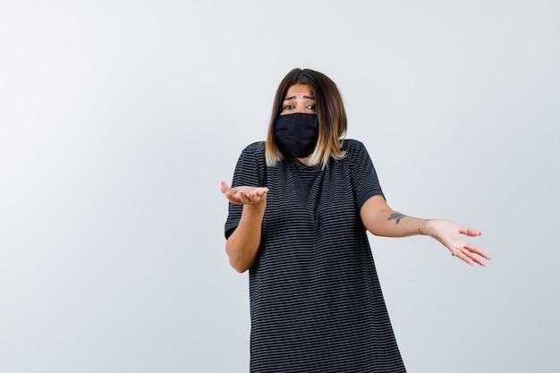 Signora che mostra gesto impotente in abito nero, mascherina medica e guardando perplesso, vista frontale.