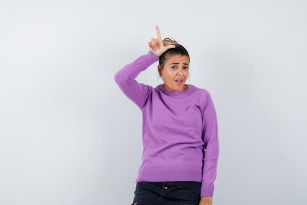 Signora che mostra il segno del perdente sopra la testa in camicetta di lana e sembra delusa
