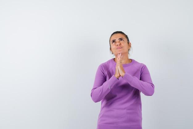 Signora che mostra il gesto di namaste in camicetta di lana e sembra speranzosa