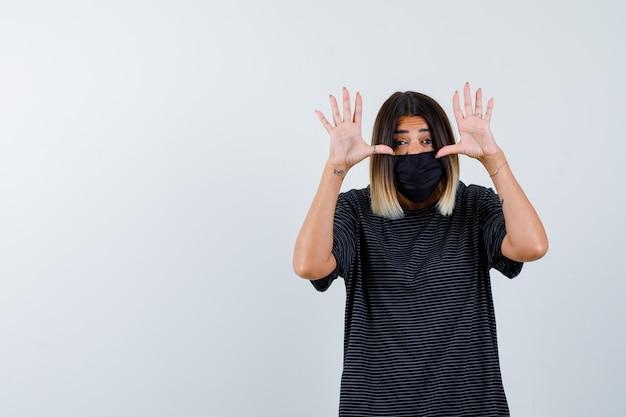 黒のドレス、医療マスク、興奮して見える、正面図で降伏ジェスチャーで手のひらを示す女性。