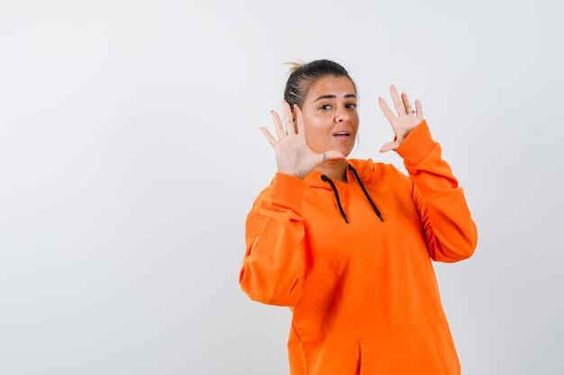 Дама в оранжевой толстовке с капюшоном показывает ладони в жесте капитуляции и выглядит уверенно