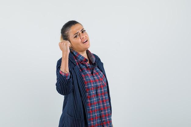 シャツ、ジャケットで上げられた握りこぶしを示し、自信を持って見える女性。正面図。