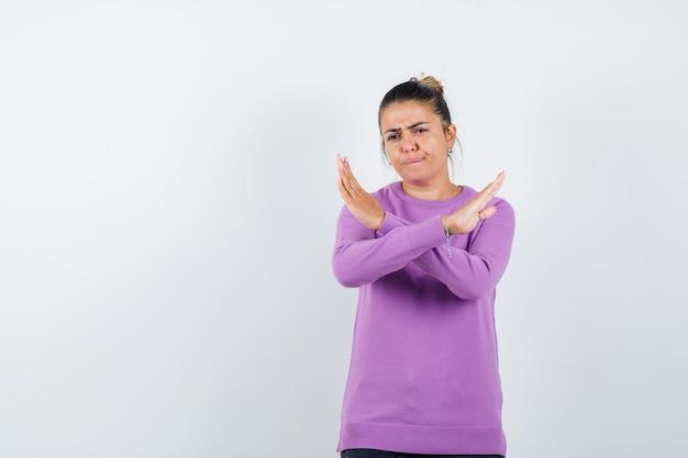 Signora che mostra gesto di rifiuto in camicetta di lana e sembra seria