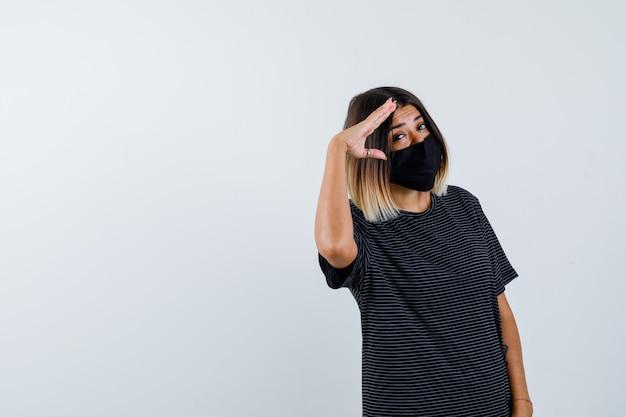 Signora che mostra gesto di saluto in abito nero, mascherina medica e guardando orgoglioso, vista frontale.
