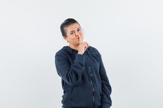 Леди показывает жест молчания в толстовке с капюшоном и выглядит уверенно. передний план.