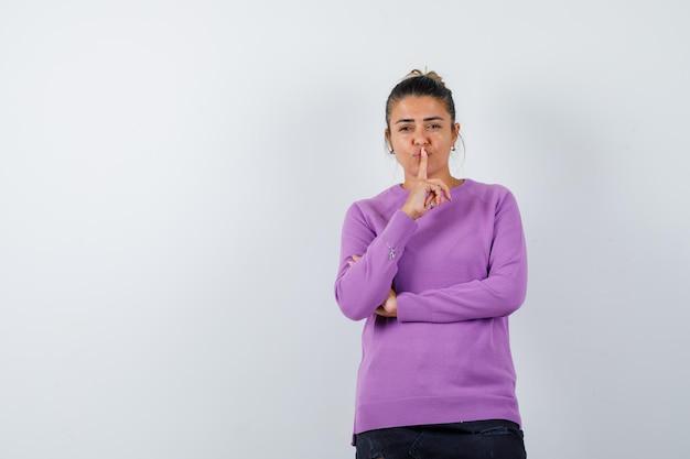 ウールのブラウスで沈黙のジェスチャーを示し、自信を持って見える女性