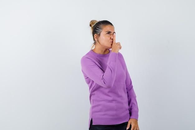 ウールのブラウスで沈黙のジェスチャーを示し、賢明に見える女性