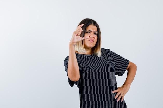 黒のtシャツで小さなサイズのサインを示し、不満を探している女性、正面図。