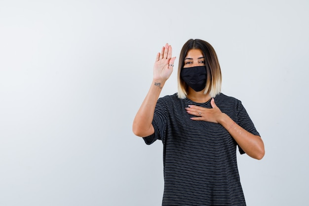 黒のドレス、医療用マスク、丁寧に見える停止ジェスチャーを示す女性。正面図。