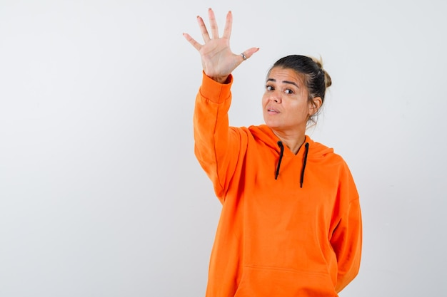 Леди показывает жест стоп в оранжевой толстовке с капюшоном и выглядит уверенно