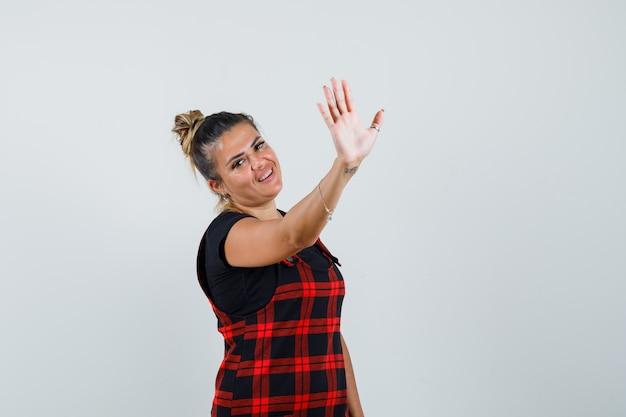 Леди показывает жест остановки в платье-сарафане и выглядит уверенно, вид спереди.