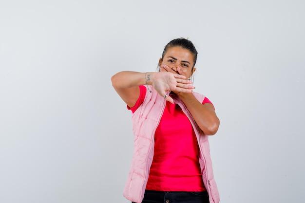 Леди показывает жест стоп в футболке, жилете и выглядит уверенно