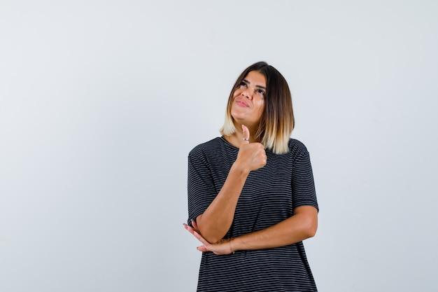 黒のtシャツに親指を立てて陽気に見える女性。正面図。