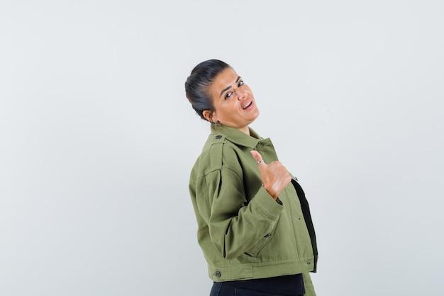 ジャケットで親指を示す女性