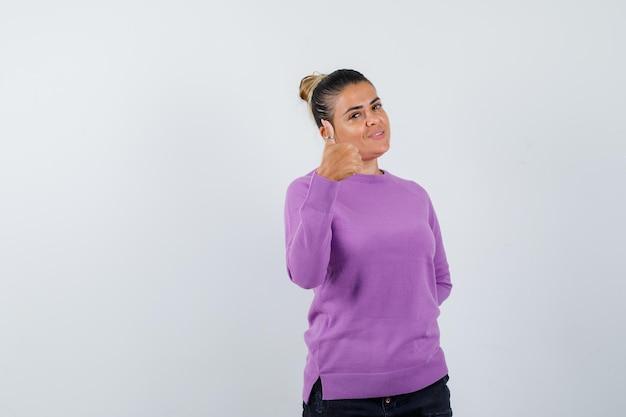 ウールのブラウスに親指を立てて自信を持って見える女性