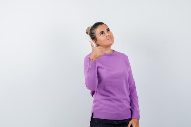 Signora che mostra pollice in su in camicetta di lana e sembra pensierosa