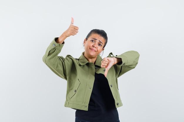 ジャケットで上下に親指を示す女性