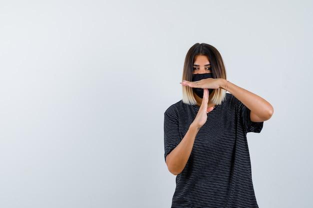 Signora che mostra il gesto di pausa di tempo in vestito nero, mascherina medica e che sembra risoluta. vista frontale.