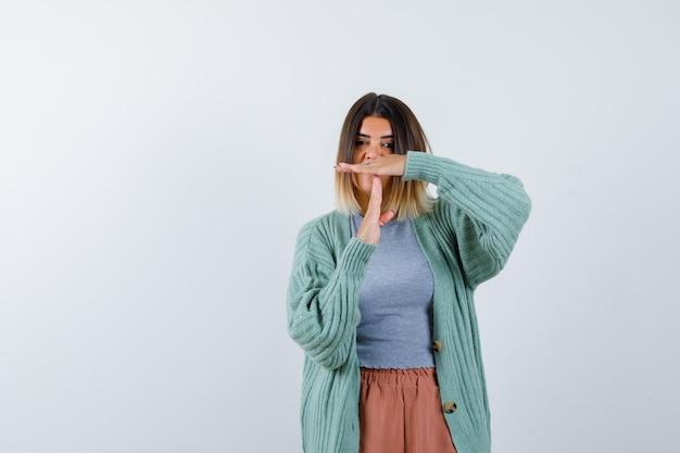 Signora che mostra il gesto della pausa di tempo in abbigliamento casual e che sembra sicura. vista frontale.