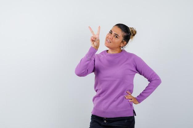 Signora che mostra il segno a v in camicetta di lana e sembra felice