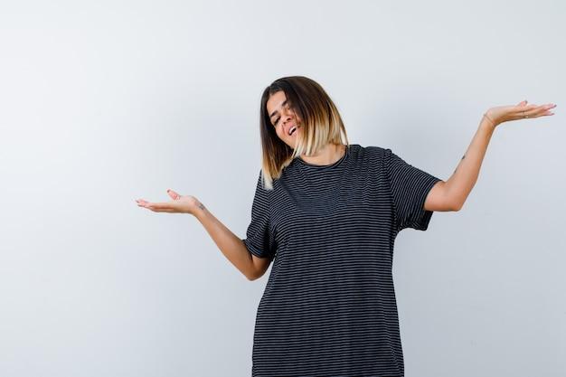 Signora che mostra gesto di benvenuto in maglietta nera e sembra felice. vista frontale.