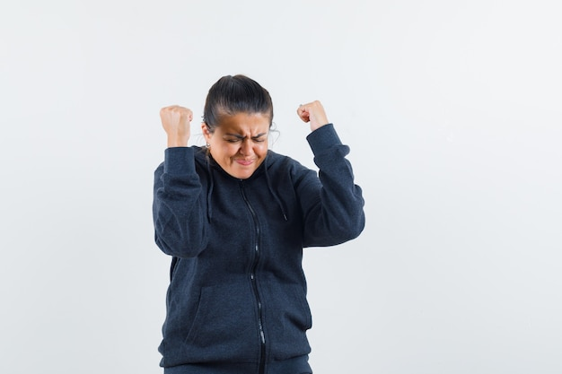 Леди показывает жест победителя в толстовке с капюшоном и выглядит удачливой