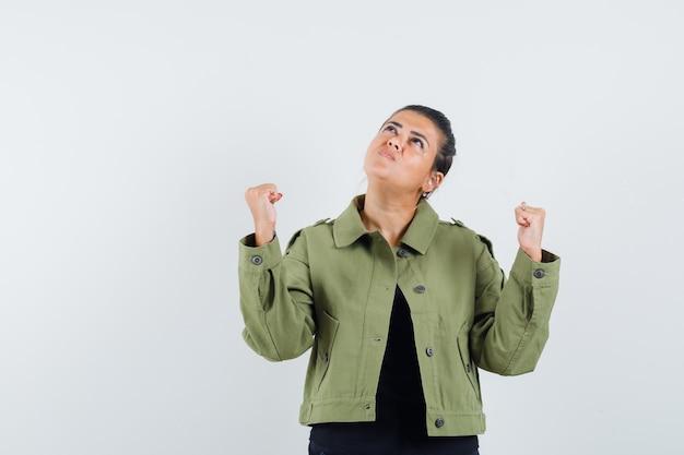 ジャケットで勝者のジェスチャーを示す女性